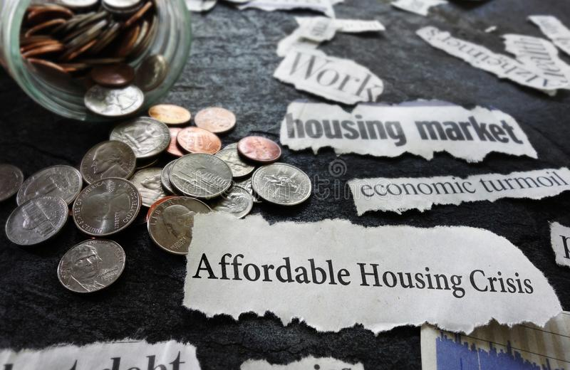 Affordable Housing Crisis news. Paper headline and related economic news, with coins royalty free stock images