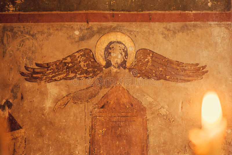 Affresco con l'angelo cieco sulla chiesa cristiana antica e luce dalla candela Simboli religiosi immagini stock libere da diritti