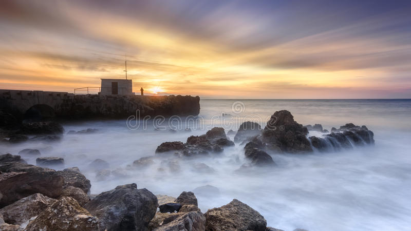 Affretti il tempo, pescatore che contempla l'alba sopra l'oceano fotografia stock