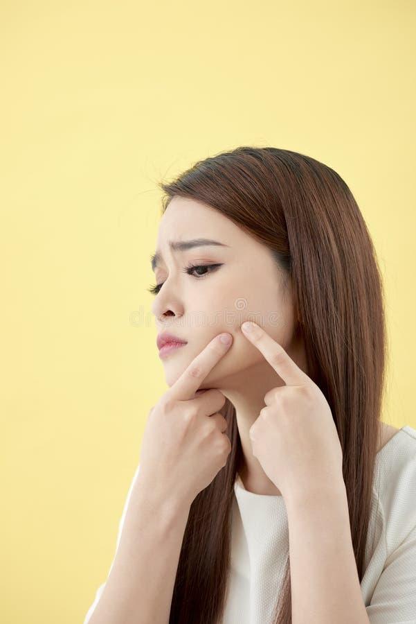 Affronti il problema di pelle - la giovane donna infelice tocca la sua pelle isolata, concetto per cura di pelle, asiatico fotografia stock libera da diritti