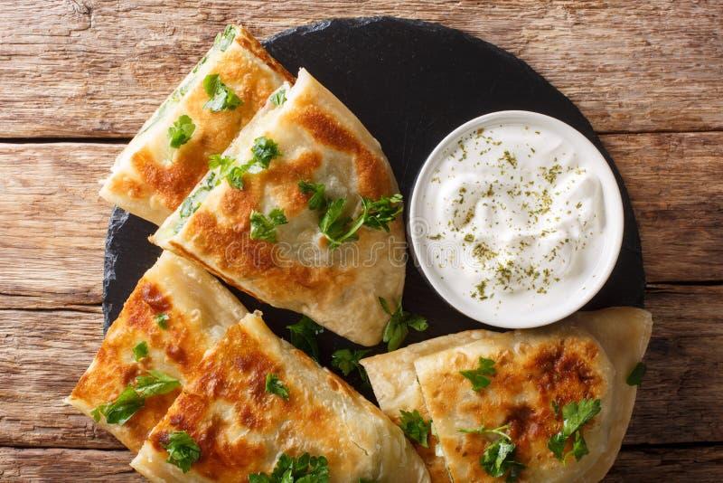 Afgańczyk smażył płaskich chleby z grulami, zielonymi cebulami i cilantro zbliżeniem, horyzontalny odg?rny widok obrazy royalty free