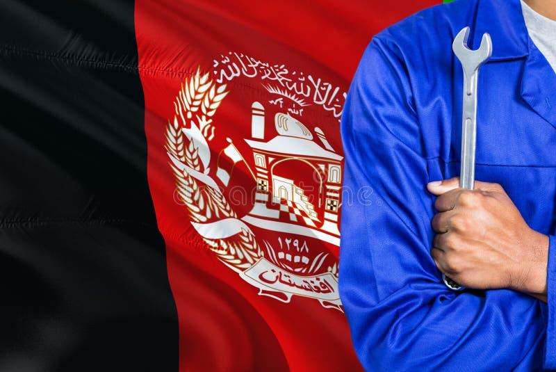 Afgański mechanik w błękita mundurze trzyma wyrwanie przeciw machać Afganistan chorągwianego tło Krzyżujący ręka technik zdjęcie royalty free