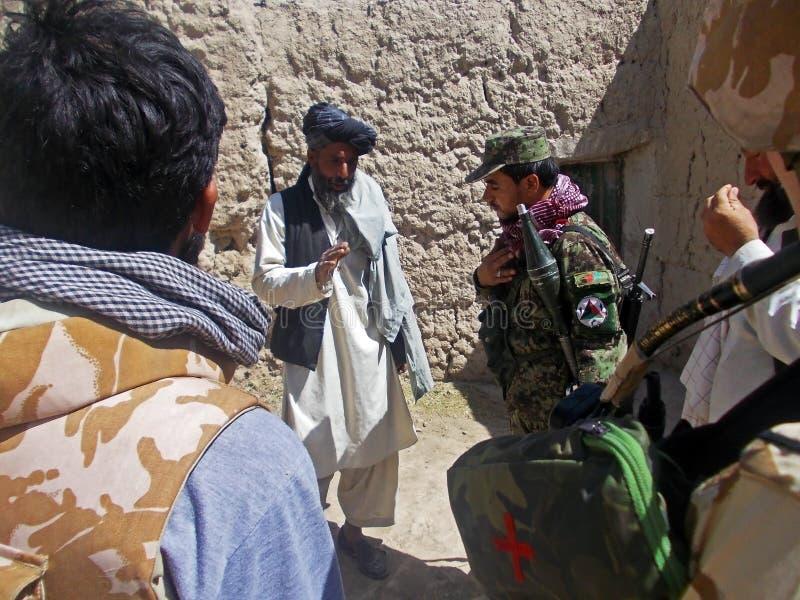 Afgański oficer wojskowy przesłuchuje miejscowego fotografia stock