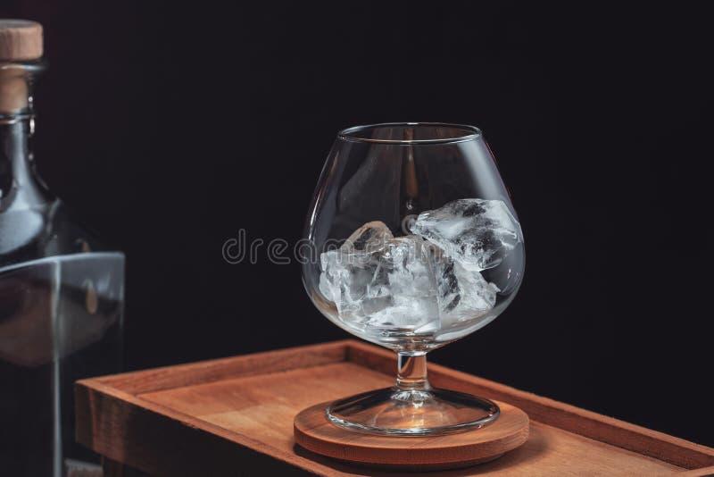 Afgebroken ijs in een transparant cognacglas, op een houten doos op een zwarte achtergrond stock fotografie