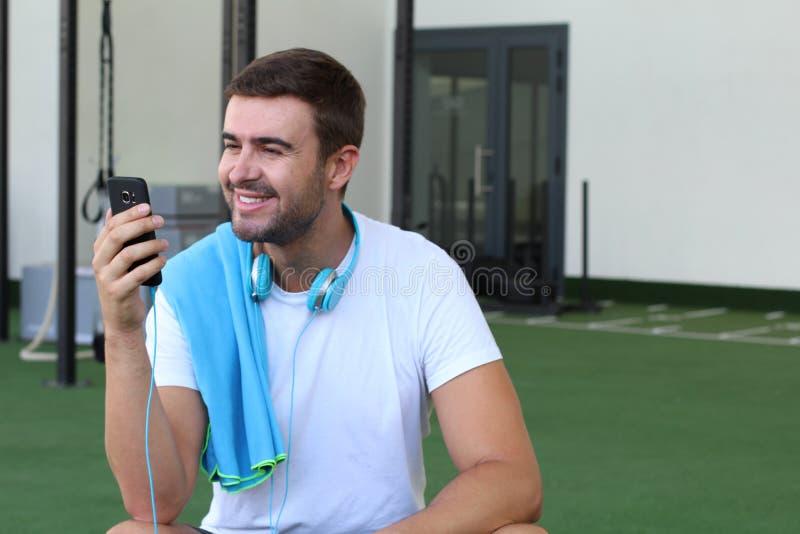 Afgeleide mens met cellphone bij de gymnastiek stock foto