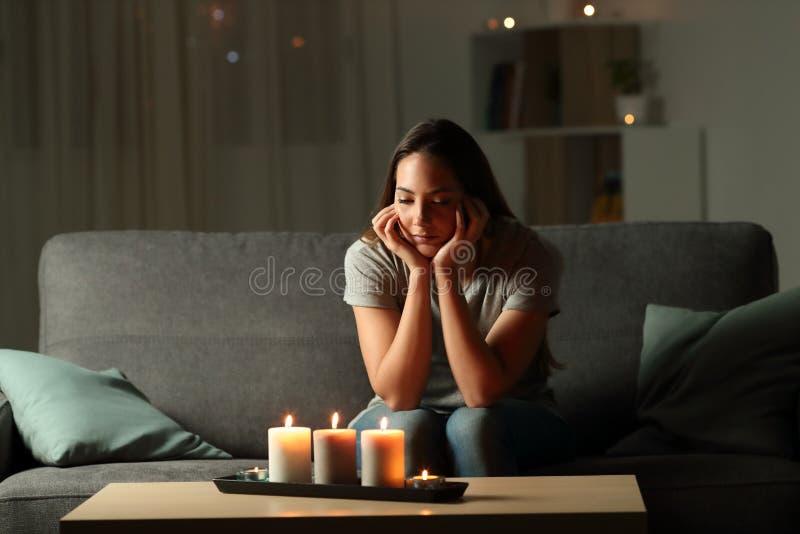 Afgeleide vrouw die kaarsenlicht tijdens elektriciteitspanne bekijken stock foto's