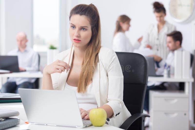 Afgeleide zwangere vrouw op het werk royalty-vrije stock foto