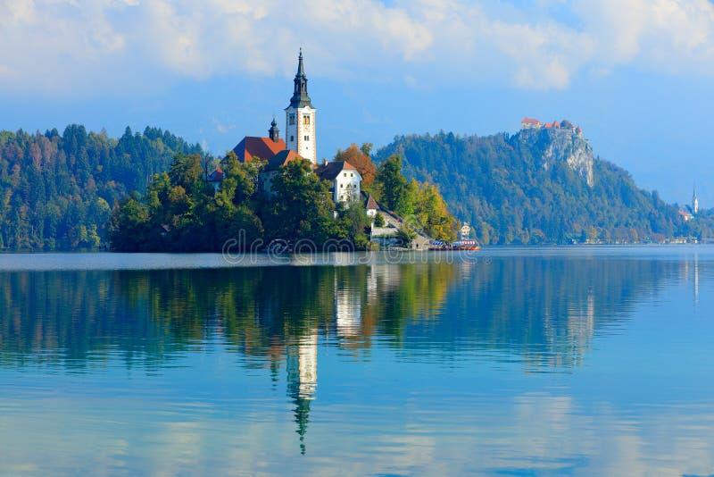 Afgetapt meereiland, St Martin Catholic kerk en Kasteel met bergketen, Slovenië, Europa Landschap in Slovenië, aard in Eur stock afbeelding