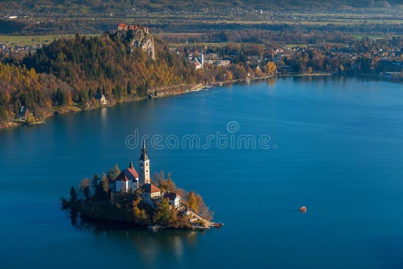 Afgetapt, Slovenië - de Zonsopgang bij meer tapte genomen vanuit Osojnica-gezichtspunt met traditionele Pletna-boot en Afgetapt K stock foto's