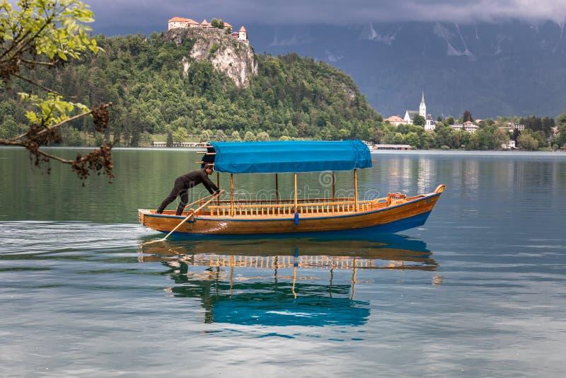 Afgetapt, Slovenië - Mei 18, 2019: mensen die een traditionele Sloveense houten boot genoemd 'pletna 'roeien voor het vervoeren v royalty-vrije stock afbeeldingen