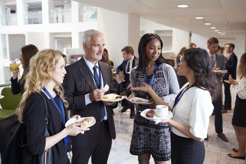 Afgevaardigdenvoorzien van een netwerk tijdens Conferentiemiddagpauze stock afbeelding