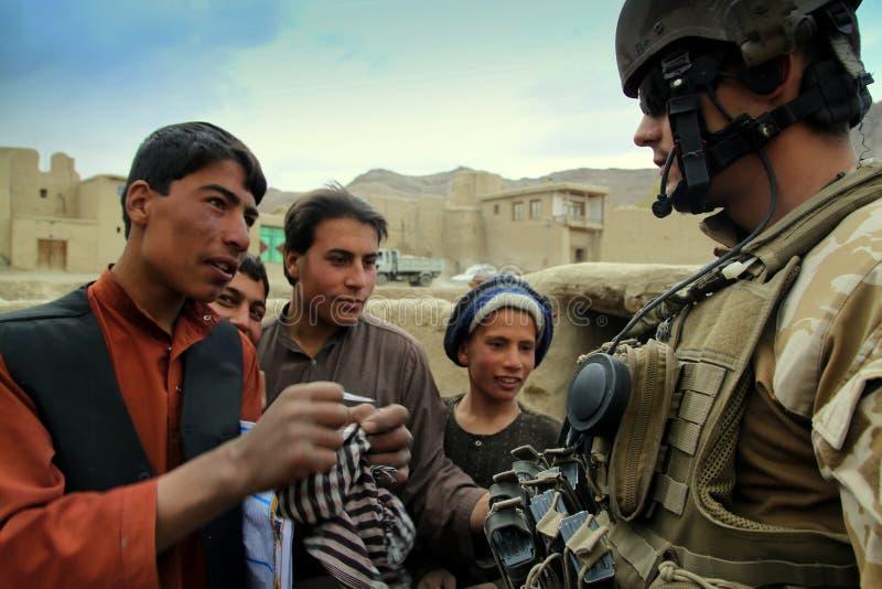 afghan argumenterar den tjeckiska soldaten för pojken arkivfoto