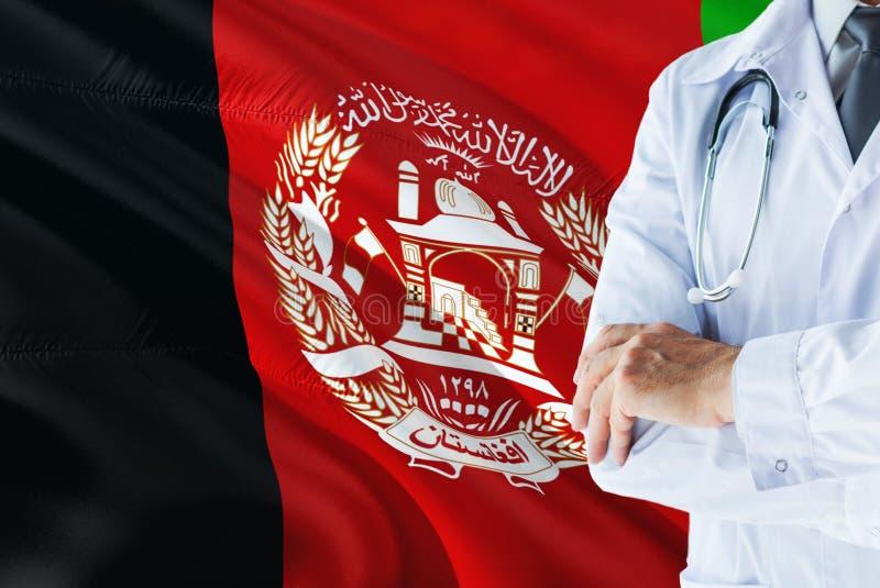 Afghanische Doktorstellung mit Stethoskop auf Afghanistan-Flaggenhintergrund Nationales Gesundheitssystemkonzept, medizinisches T stockbilder