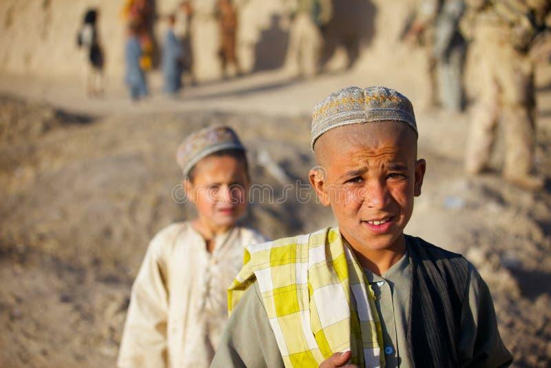 Afghanische Kinder passen eine überschreitene Patrouille auf stockfotografie