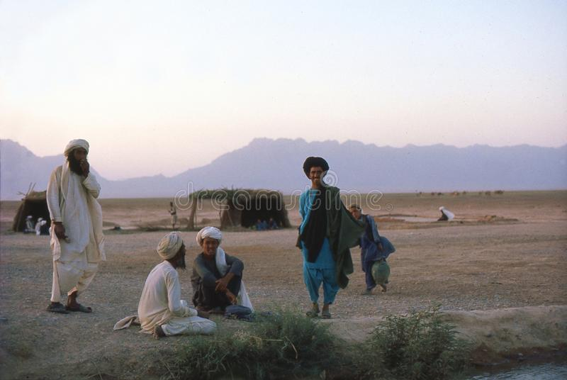 1975. Afghanistan. Afghan nomads. The photo shows, some friendly afghan nomads, having a conversation. Notice, the boy who is on the way to collect water. The stock photos