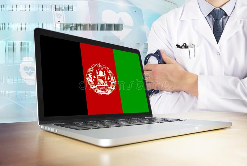 Afghanistan healthcare system in tech theme. Afghan flag on computer screen. Doctor standing with stethoscope in hospital. Cryptocurrency and Blockchain royalty free stock images