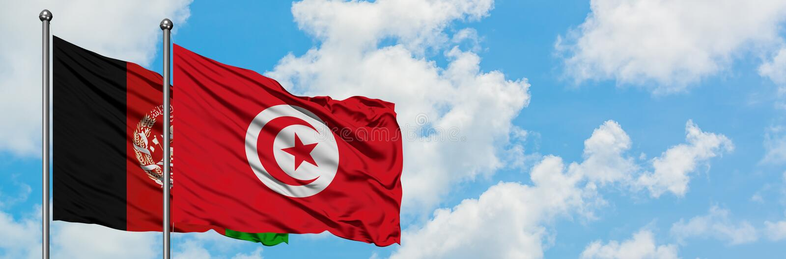 Afghanistan and Tunisia flag waving in the wind against white cloudy blue sky together. Diplomacy concept, international relations.  stock photos