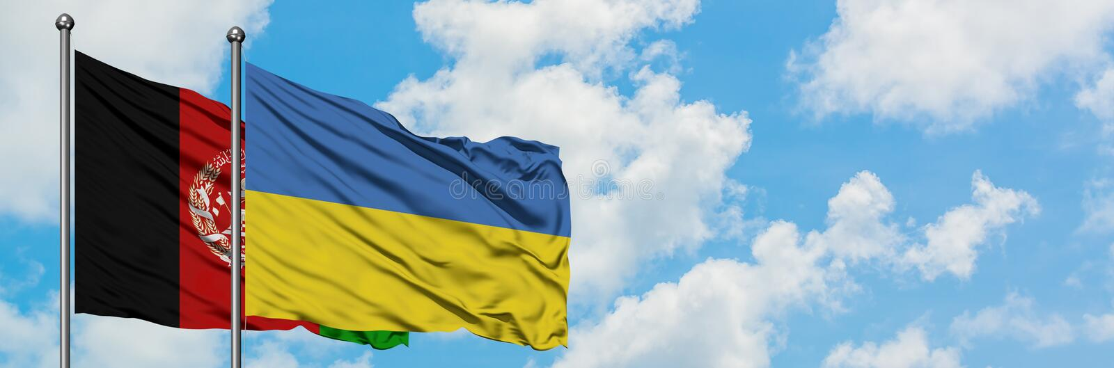 Afghanistan and Ukraine flag waving in the wind against white cloudy blue sky together. Diplomacy concept, international relations.  stock photography