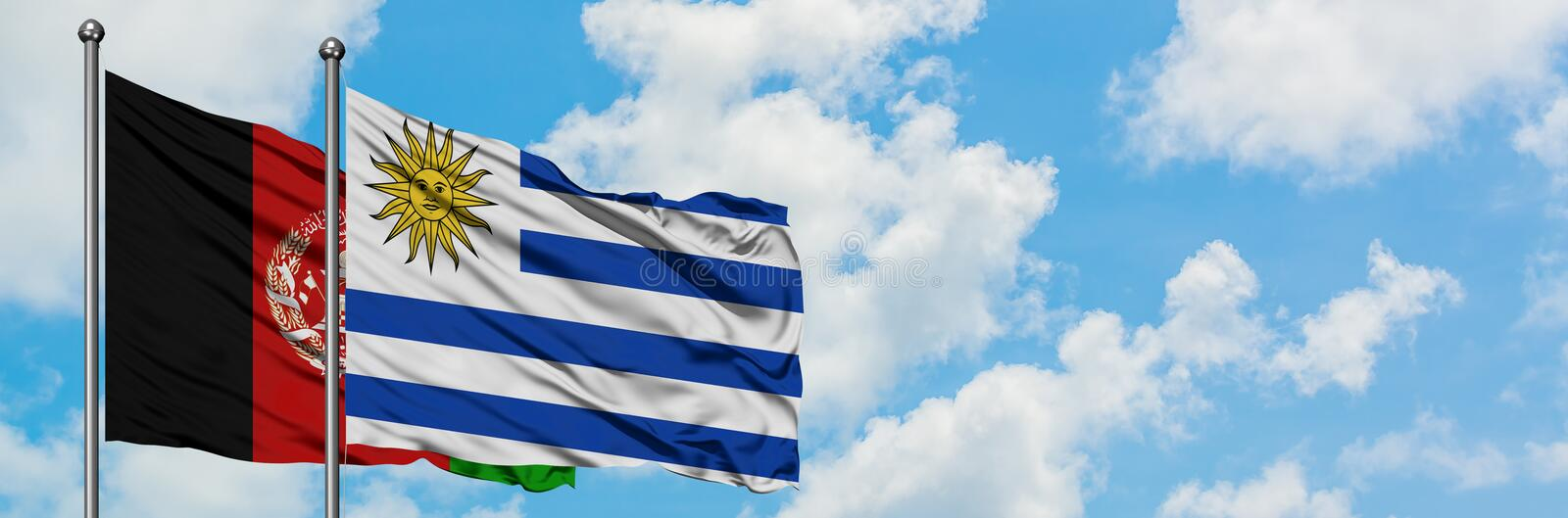 Afghanistan and Uruguay flag waving in the wind against white cloudy blue sky together. Diplomacy concept, international relations.  stock photography