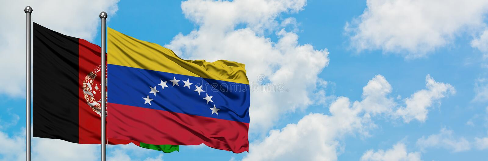 Afghanistan and Venezuela flag waving in the wind against white cloudy blue sky together. Diplomacy concept, international. Relations stock photo