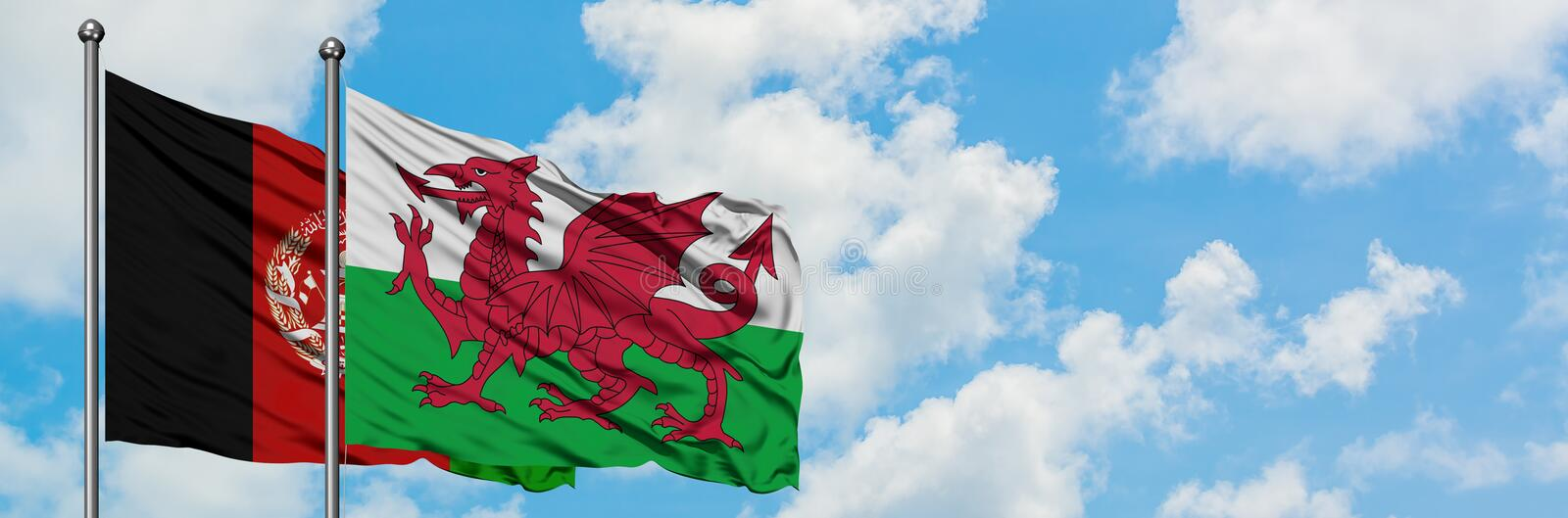 Afghanistan and Wales flag waving in the wind against white cloudy blue sky together. Diplomacy concept, international relations.  royalty free stock photos
