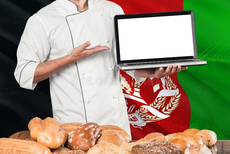 Afghansk bagareinnehavbärbar dator på den Afghanistan flaggan och brödbakgrund Bärande likformig för kock som pekar den tomma skä arkivbilder