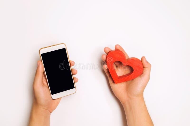 Afhankelijkheid van sociale netwerken telefoonsmartphone en hart in handen het dateren online, het flirten, bericht en het roepen stock foto