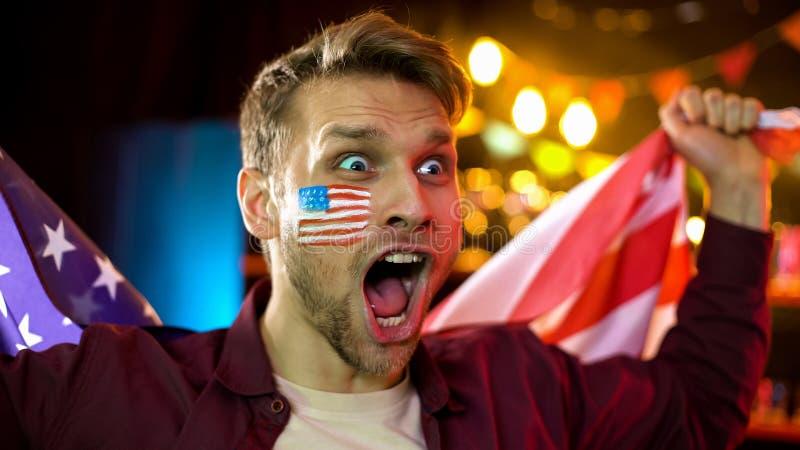 Aficionado al béisbol feliz con la bandera pintada en la mejilla que grita, celebrando la victoria foto de archivo libre de regalías