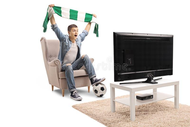 Aficionado al fútbol adolescente extático que sostiene una bufanda y que mira un matc imágenes de archivo libres de regalías