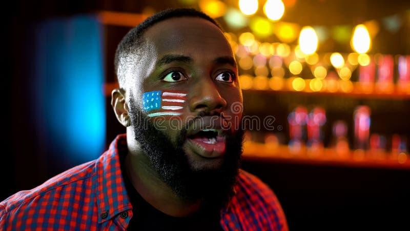 Aficionado al fútbol afroamericano nervioso con la bandera en la mejilla infeliz con resultado del juego foto de archivo