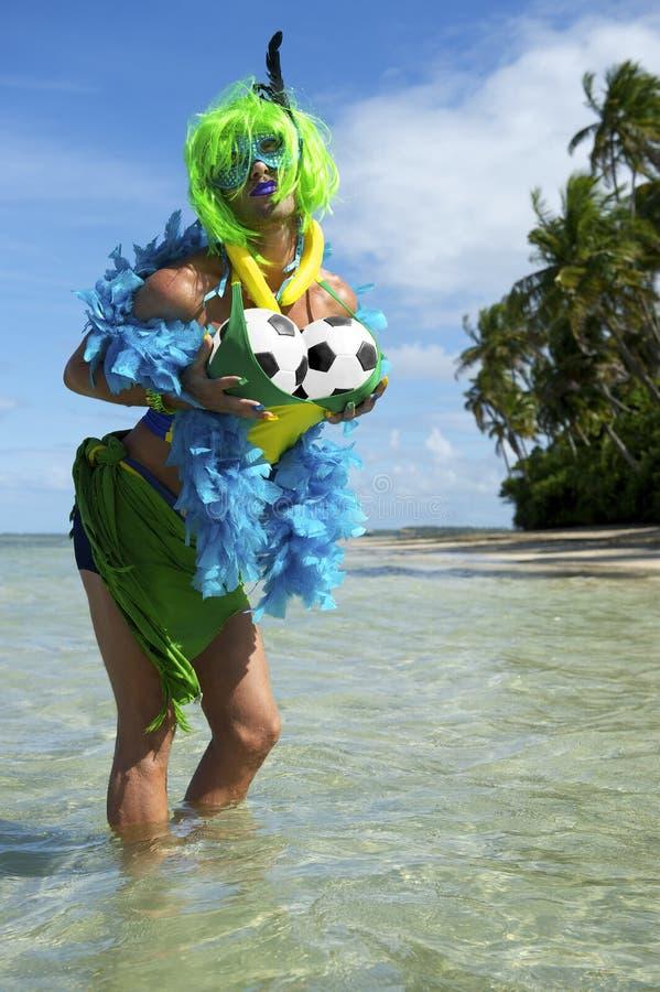 Aficionado al fútbol brasileño divertido en la playa imagen de archivo libre de regalías