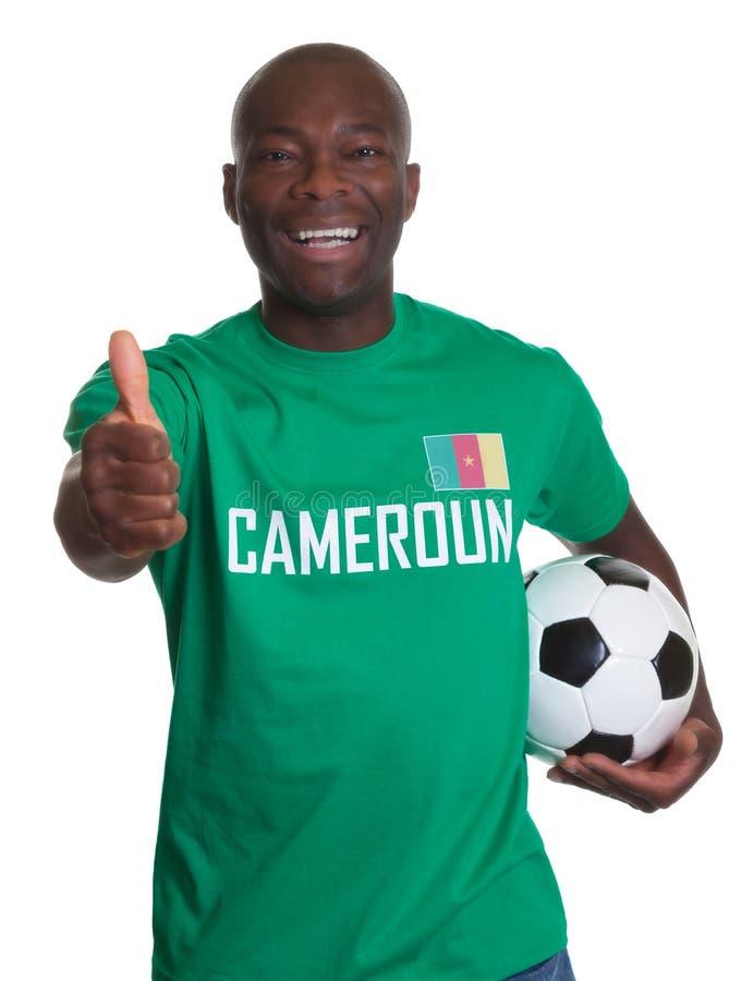 Aficionado al fútbol del Camerún con el fútbol que muestra el pulgar para arriba imagen de archivo