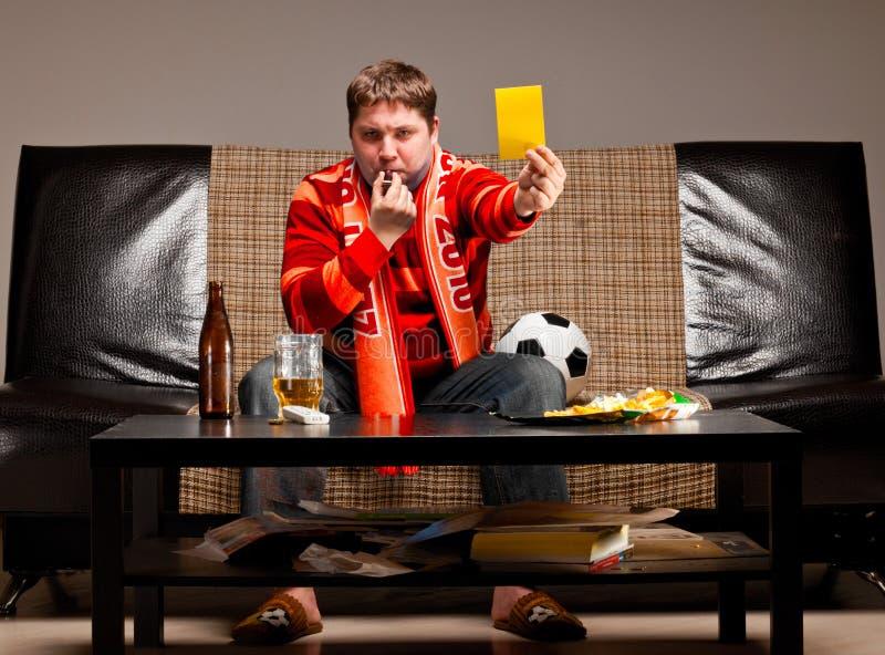 Aficionado al fútbol en el sofá imagen de archivo libre de regalías