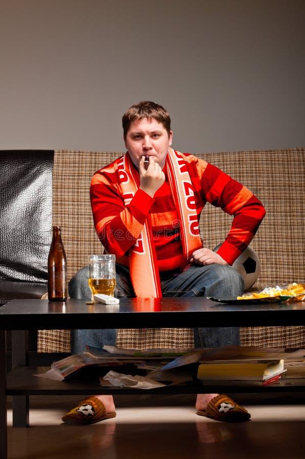 Aficionado al fútbol en el sofá fotografía de archivo