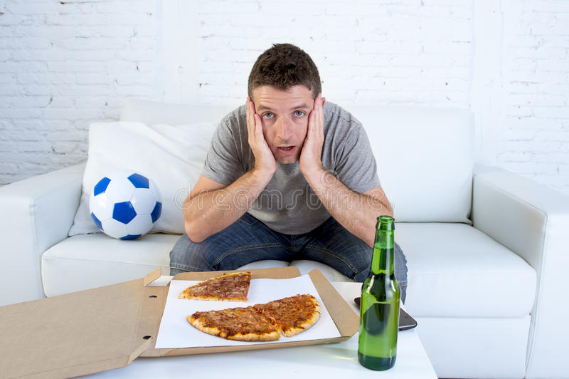 Aficionado al fútbol en partido de fútbol de observación de la tensión en la televisión en sofá del sofá con la caja de la pizza  fotos de archivo