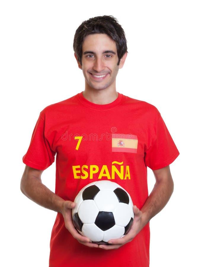 Aficionado al fútbol español feliz con el pelo negro y la bola fotografía de archivo