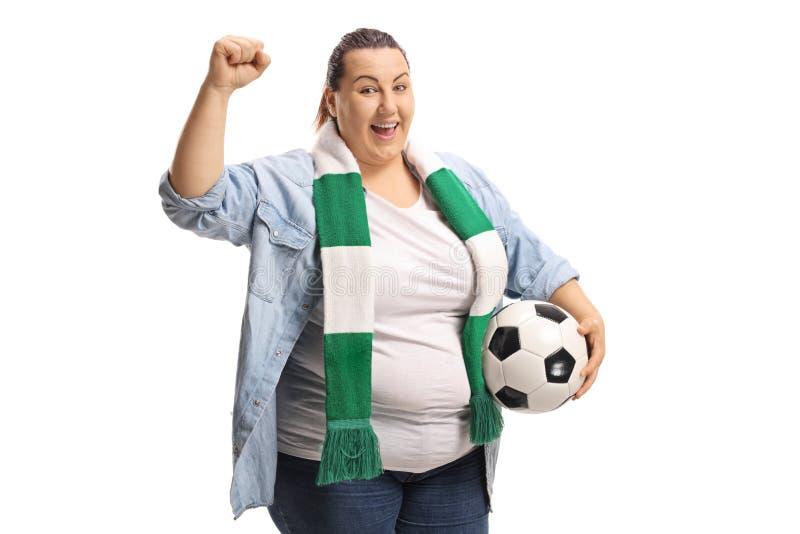 Aficionado al fútbol femenino alegre con una bufanda y un fútbol que gesticulan w imagen de archivo libre de regalías