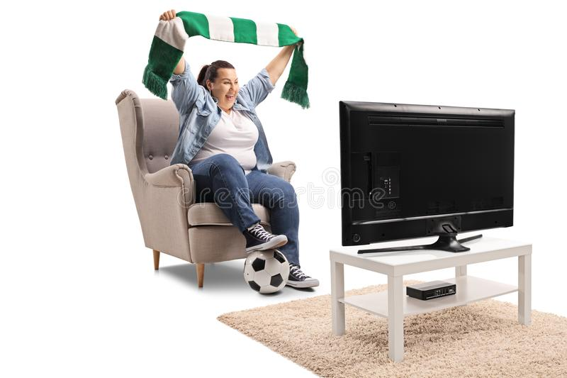 Aficionado al fútbol femenino emocionado que sostiene una bufanda y que mira un partido o foto de archivo libre de regalías