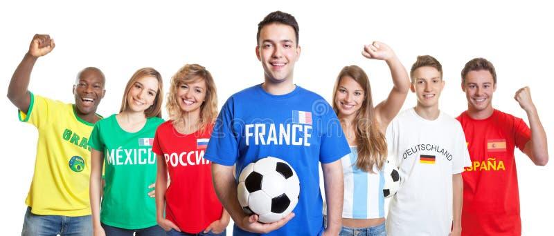 Aficionado al fútbol francés alegre con la bola y fans del otro countri foto de archivo