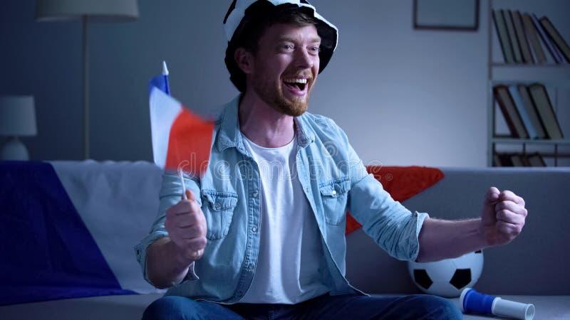 Aficionado al fútbol francés con el juego de observación de la bandera en la TV, celebrando meta, competencia fotografía de archivo libre de regalías