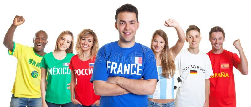 Aficionado al fútbol francés con los brazos y las fans cruzados del otro país imagen de archivo libre de regalías