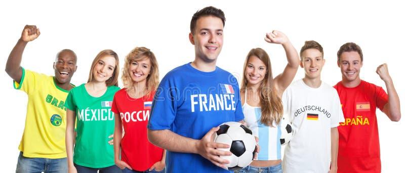 Aficionado al fútbol francés feliz con la bola y fans de otros países imágenes de archivo libres de regalías