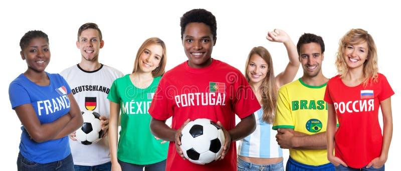 Aficionado al fútbol portugués con la bola y el grupo que anima de otras fans foto de archivo libre de regalías