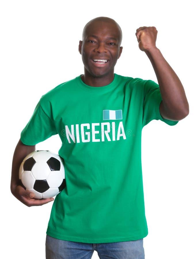 Aficionado al fútbol que anima de Nigeria con la bola foto de archivo