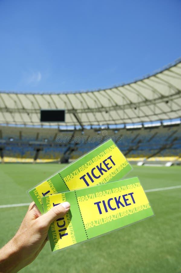 Aficionado al fútbol que celebra dos boletos del Brasil en el estadio foto de archivo libre de regalías