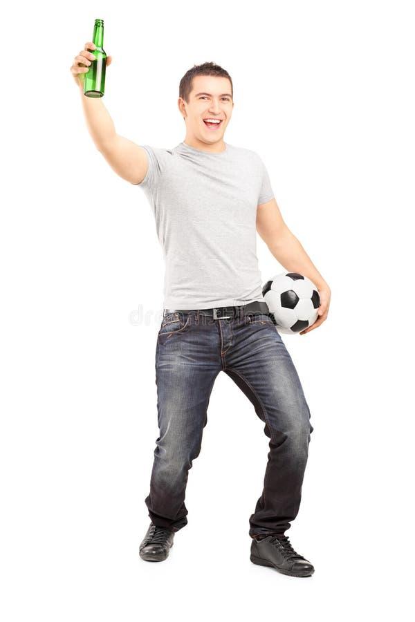 Aficionado deportivo eufórico que lleva a cabo una botella y un fútbol de cerveza fotografía de archivo libre de regalías