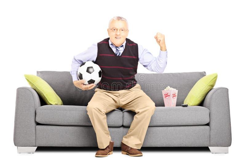 Aficionado deportivo maduro que sostiene un balón de fútbol y que mira deporte foto de archivo libre de regalías