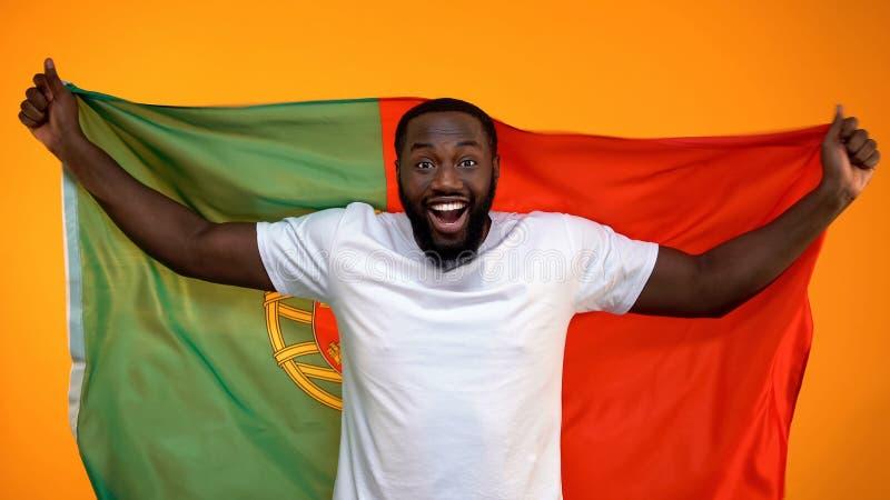 Aficionado desportivo afro-americano surpreendido que guarda a bandeira portuguesa, cheering para a vit?ria foto de stock royalty free