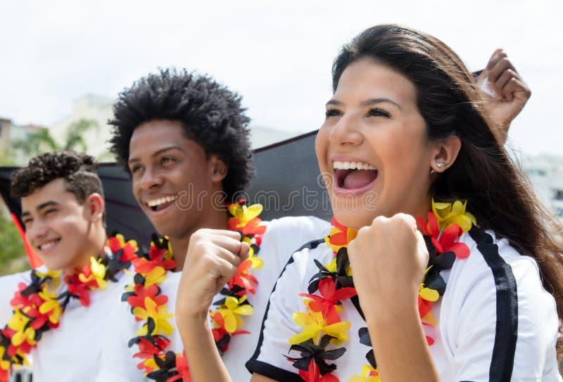 Aficionados al fútbol alemanes felices sobre una meta del equipo nacional fotos de archivo