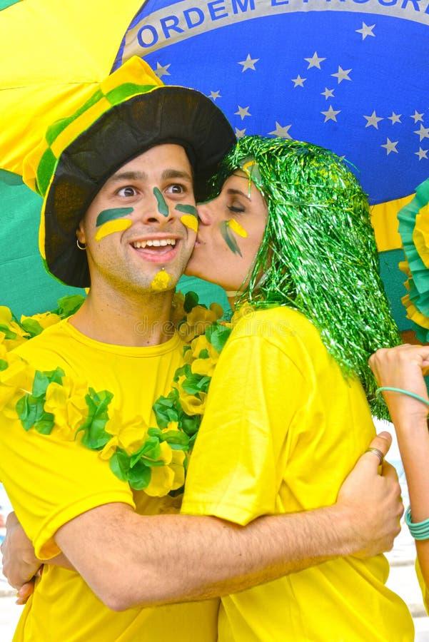 Aficionados al fútbol brasileños de la mujer que conmemoran besarse de la victoria. imágenes de archivo libres de regalías